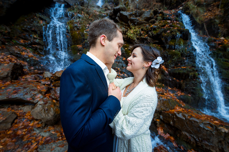 lovingly: Lovely wedding couple softly holding hands and lovingly look at each other. Waterfall on background. Stock Photo