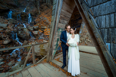 a meeting with a view to marriage: Charming wedding couple hugs on the wooden bridge in mountains. Waterfall background.