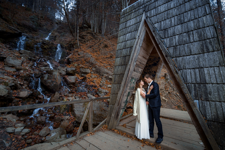 a meeting with a view to marriage: Beautiful wedding couple hugs on the wooden bridge in mountains. Waterfall background.