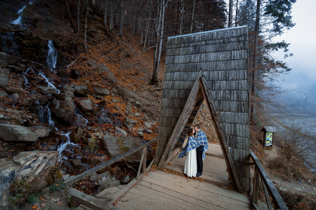 a meeting with a view to marriage: Wedding couple softly kiss on the wooden bridge. Misty day in mountains. Stock Photo