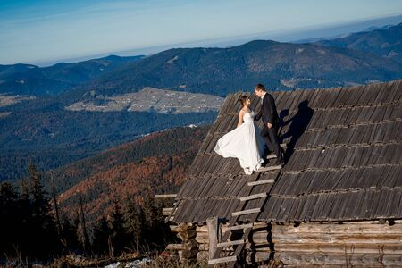 honeymoon: Beautiful wedding couple standing on the roof of country house. Amazing mountain landscape on background. Honeymoon. Stock Photo