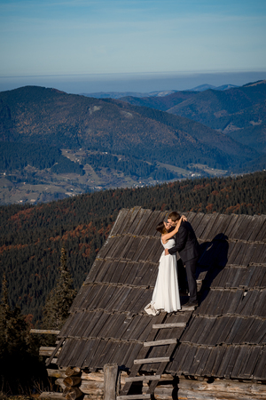 honeymoon: Charming wedding couple kissing on the roof of country house. Amazing mountain landscape on background. Honeymoon.