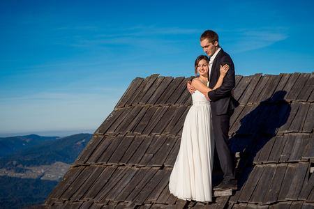 happy couple house: Happy wedding couple  posing on the roof of country house. Amazing mountain landscape on background. Honeymoon.