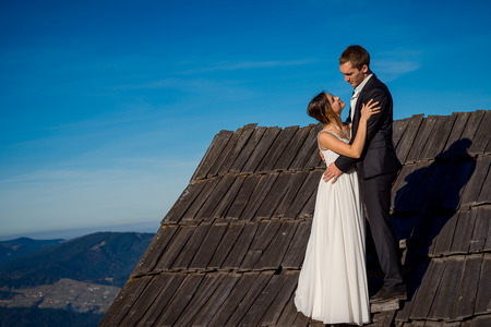 softly: Young wedding couple softly hugs on the roof of country house. Wonderful mountain landscape background. Stock Photo