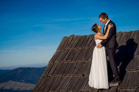 honeymoon: Happy newlyweds hugging on the roof of country house. Wonderful mountain landscape background. Honeymoon.