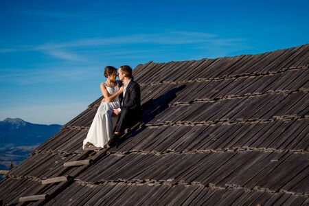 honeymoon: Happy newlyweds sitting on the roof of country house. Honeymoon in mountains. Stock Photo