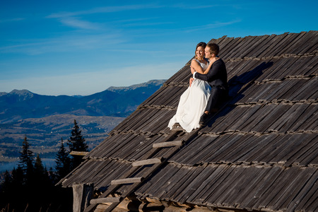 honeymoon: Wedding couple sitting on the roof of country house. Honeymoon in mountains.