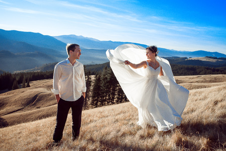 gracefully: Bride and groom dancing on the mountain. Honeymoon in Alps.