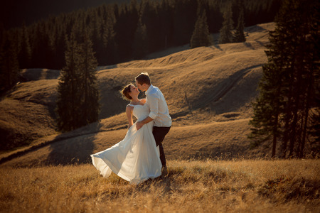 parejas amor: Encantadora pareja besándose boda. Hermoso paisaje de montaña en el fondo.