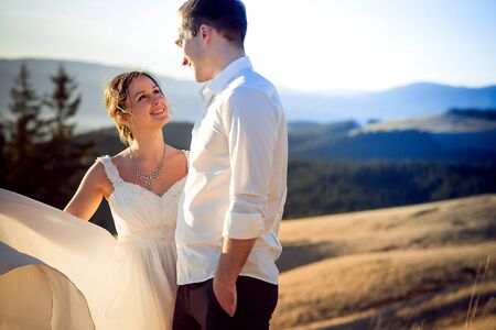 lovingly: Bride and groom lovingly look at each other. Mountains background.