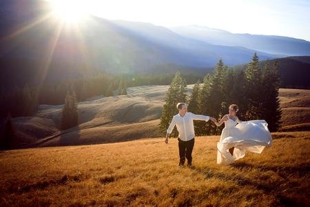 matrimonio feliz: Hermosa pareja de novios se ejecuta y divertirse en el campo rodeado de montañas. Foto de archivo