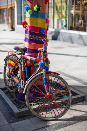 parked: Funny retro colorful bicycle parked at the bright knitted tree. Stock Photo