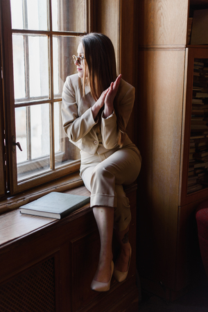 well read: Beautiful stylish business lady in glasses reads a book on the windowsill.