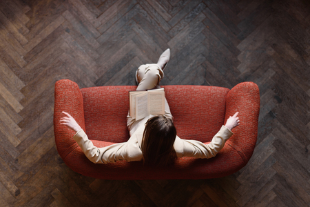 Stylish young girl in beige suit reads a book on the red sofa. Top view.