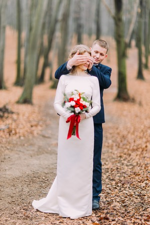 closes eyes: Groom closes eyes to his beautiful bride in the autumn forest.