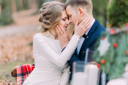 Charming wedding couple softly stroking face of each other at the holiday table in autumn forest. Stock Photo