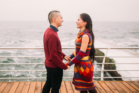 lovingly: Bright stylish couple holding hands and lovingly look at each other on the berth. Sea background. Wonderful honeymoon.