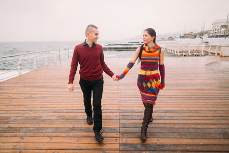 lovingly: Beautiful young creative couple in love walking on the rainy berth and lovingly look at each other. Sea background.