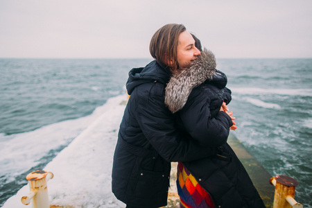 stoned: Beautiful young couple tenderly hugging on stoned pier during rainy autumn day. Winter sea background. Stock Photo