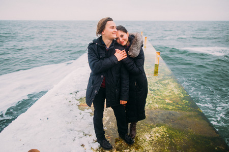stoned: Rear romantic view of a young couple posing on a stoned pier during a rainy autumn day. Winter sea background.