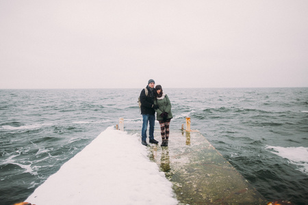 old pier: Happy young couple run towards each other on the old pier with beautiful winter sea background.