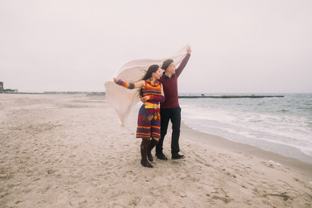brunete: Attractive young happy couple wrapped in white blanket walking on the winter beach and looking at water. Vintage concept.