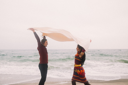 Funny young happy couple under the white blanket having fun and  playfully look at each other. Winter beach on background. Vintage concept.
