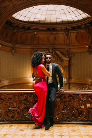 Beautiful african couple posing in the luxurious theatre interior. Banco de Imagens