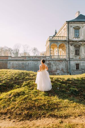 updo: Elegant bride with brown short hair updo and bare shoulders white wedding dress view from the back near old mansion at sunset.