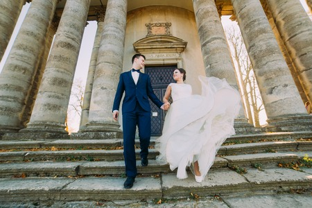 down the stairs: Romántica pareja casada novia y el novio caminando por las escaleras fondo antiguo Builing.