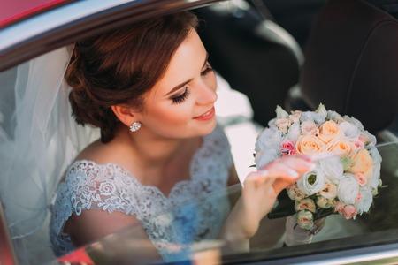 有美丽的微笑的华美的新娘坐在婚礼汽车和拿着夏天花花束。