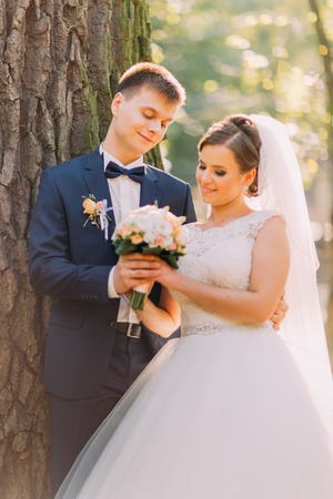 a newly married couple: A newly married couple hold hands with bouquet of flowers and look with eyes full of love at each other. Stock Photo
