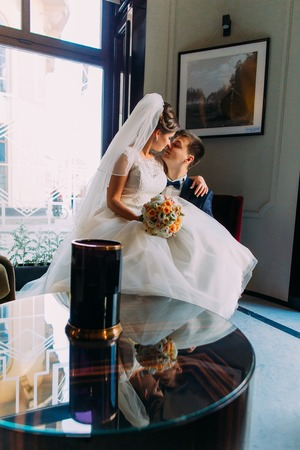 lap of luxury: Bride and groom sitting in a room in a luxurious chair on his knees. The woman in a beautiful wedding dress. A man in a suit and bow-tie. Loving couple together indoors.