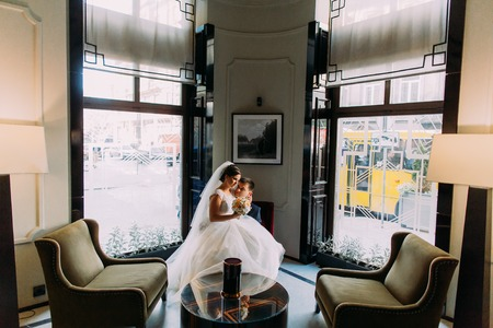 lap of luxury: Bride  sitting in a luxurious chair on grooms knees.