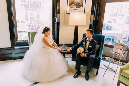 ceremonial clothing: bride and groom sitting in the lobby of the hotel. In the hands of the bride holding a bouquet Stock Photo