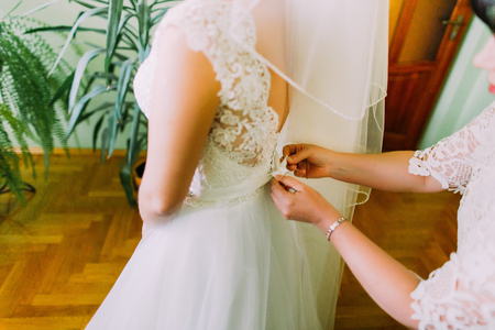 Mother helping the bride - her daughter to put her wedding dress on, close up photo Banque d'images