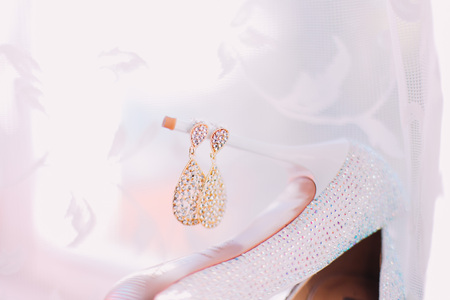 Female wedding accessories golden earrings over white veil background.