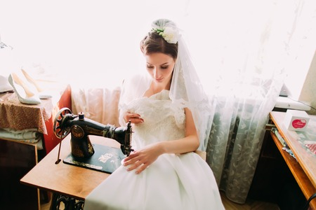 Beautiful young bride makes last minute adjustments to her Wedding Dress at an ancient old treadle sewing machine. Standard-Bild