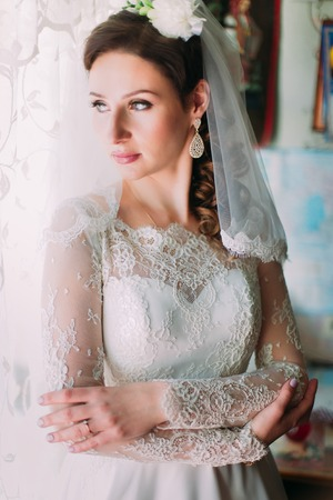 thick hair: Portrait of a young woman with chic thick hair, wearing a white dress looking toward the window, in profile. Stock Photo