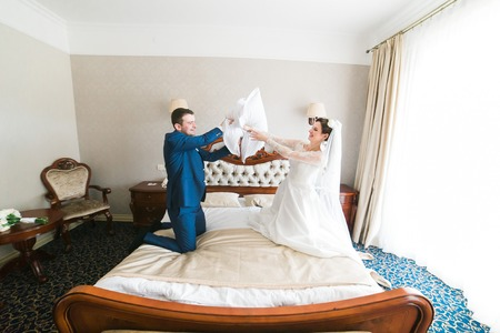 bridegrooms: Portrait of happy newlywed couple fighting with pillows on bed in hotel room