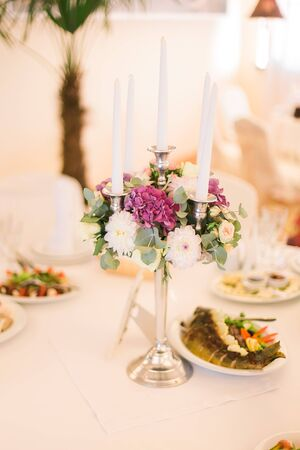 vintage cutlery: Festive wedding table setting with pink flowers, napkins, vintage cutlery, glasses and candles, bright summer table decor. Stock Photo
