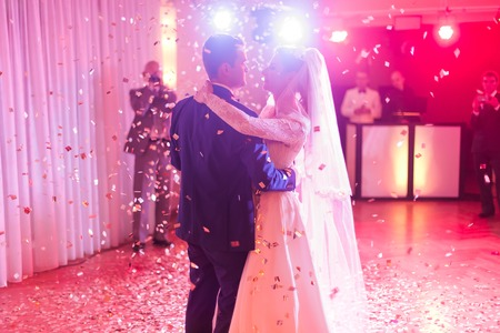 Brides wedding party in the elegant restaurant with wonderful light and atmosphere. Beautiful married couple dancing.