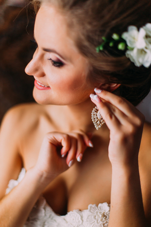 bridal gown: Beautiful bride in white wedding dress puts on earring. Beauty model girl is wearing jewelry. Female portrait in bridal gown for marriage. Woman with curly hair and lace veil. Cute lady indoors