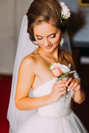 bridal gown: Beauty bride in bridal gown with bouquet indoors. Beautiful model girl in a white wedding dress. Female portrait of cute lady. Woman with hairstyle Stock Photo