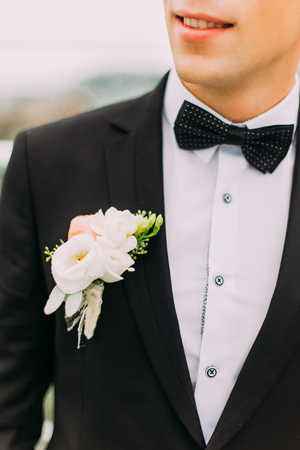 lapel: Close-up black jacket groom on their wedding day with bow-tie and lapel buttonhole.
