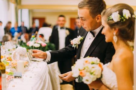 redemption: Handsome groom holding redemption of bride on wedding indoors.