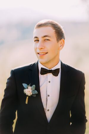 on looker: Close up portrait of handsome stylish groom outdoor with black tuxedo and bowtie. Stock Photo