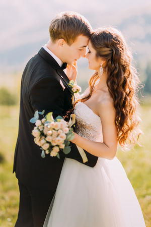 rubbing noses: Newlywed young bride and groom with flower bouquet rubbing noses