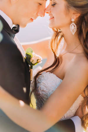 rubbing noses: Close-up photo of newlywed young bride and groom with flower bouquet rubbing noses outdoors.