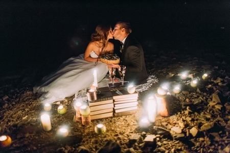 romantic beach: Loving couple share a romantic dinner with candles and cake  at beach, coast against wonderful night. Stock Photo